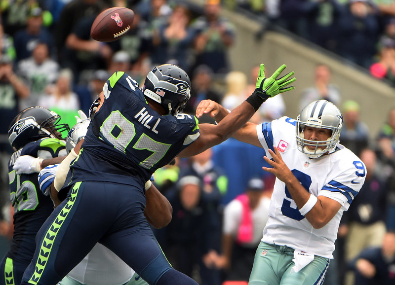 . Quarterback Tony Romo #9 of the Dallas Cowboys passes the ball as defensive tackle Jordan Hill #97 of the Seattle Seahawks applies pressure during the third quarter of the game at CenturyLink Field on October 12, 2014 in Seattle,Washington. (Photo by Steve Dykes/Getty Images)