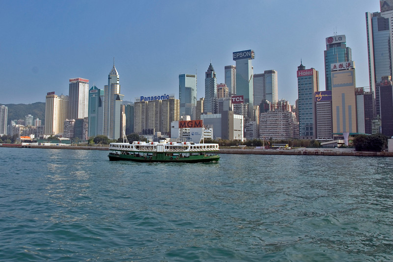 Ferry carrying passengers along the Victoria Harbor on beautiful day in Hong Kong