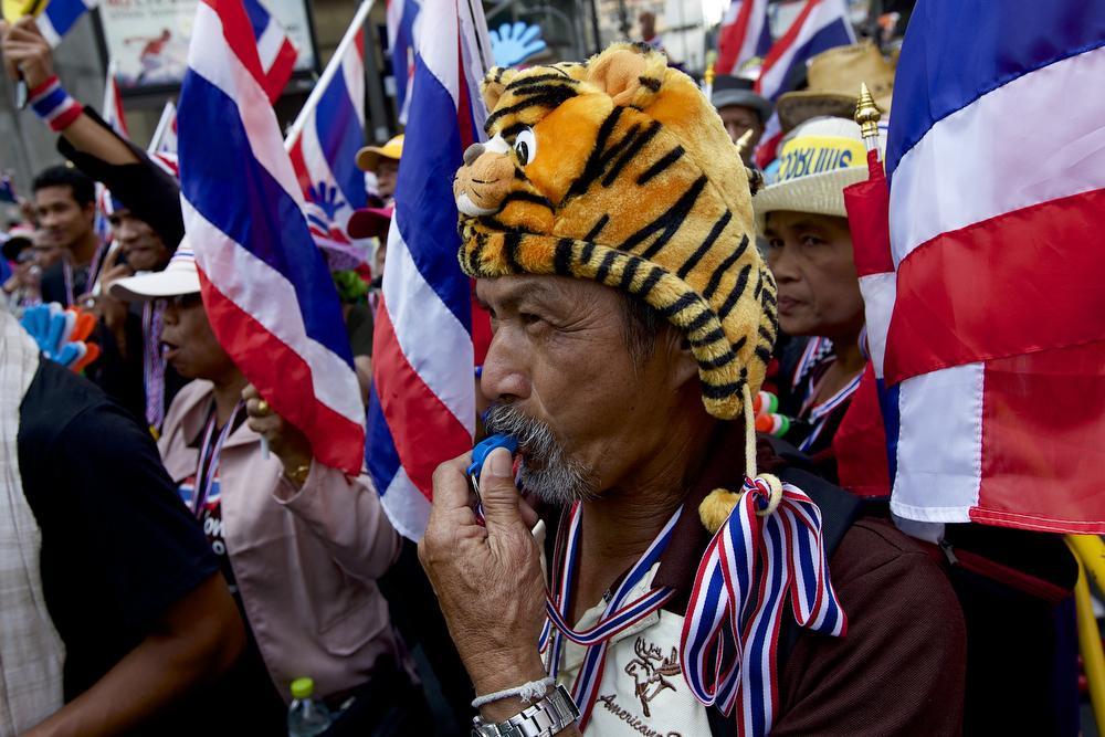 """. An anti-government protester blows his whistle, a symbol of the anti-government protesters, at the start of a march through the city on January 16, 2014 in Bangkok, Thailand.  The protesters have stepped up their activity with more rally sites  and daily marches on government ministries in an attempt to \""""shutdown Bangkok\"""" in order to pressure the government of Thai PM Yingluck Shinawatra to step down.  (Photo by Ed Wray/Getty Images)"""