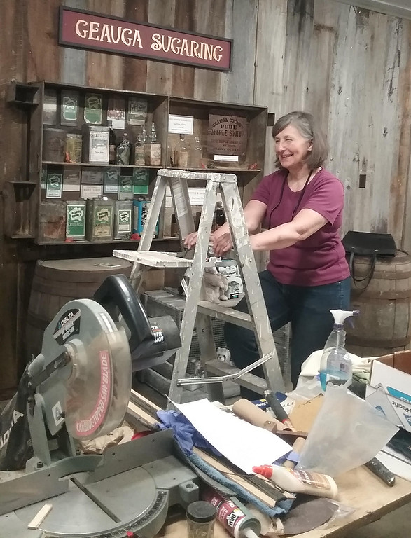 . Louise Jackson, chairperson of the Geauga County Historical Society Collection Committee, is shown just days before the Maple Museum\'s grand opening as finishing touches are made. (Jean Bonchak)