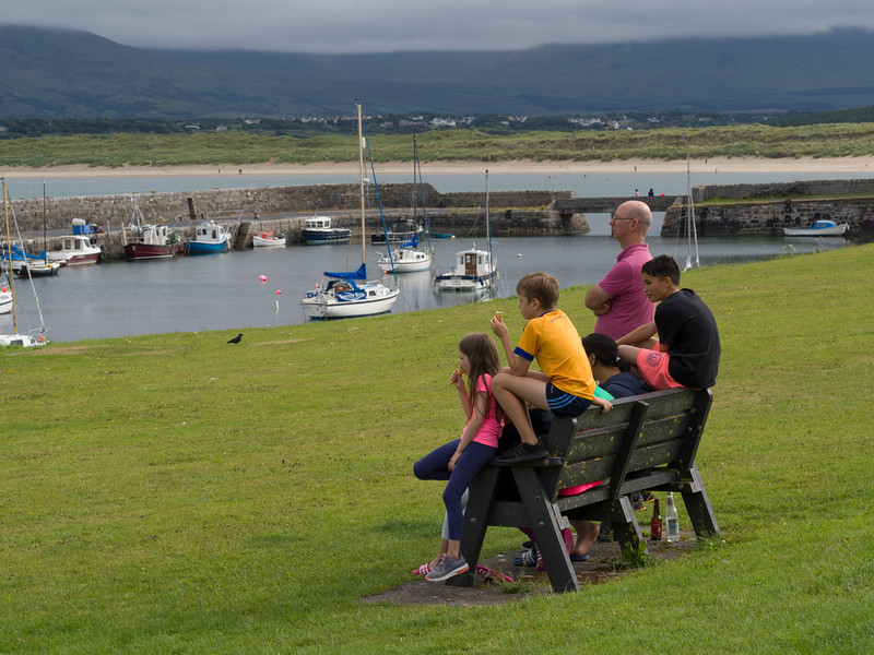 Tourists enjoying ice-cream on bench at harbor, Village of Mullaghmore, Grange, County Sligo, Republic of Ireland