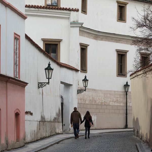 Couple walking together on cobblestone street, Prague, Czech Republic