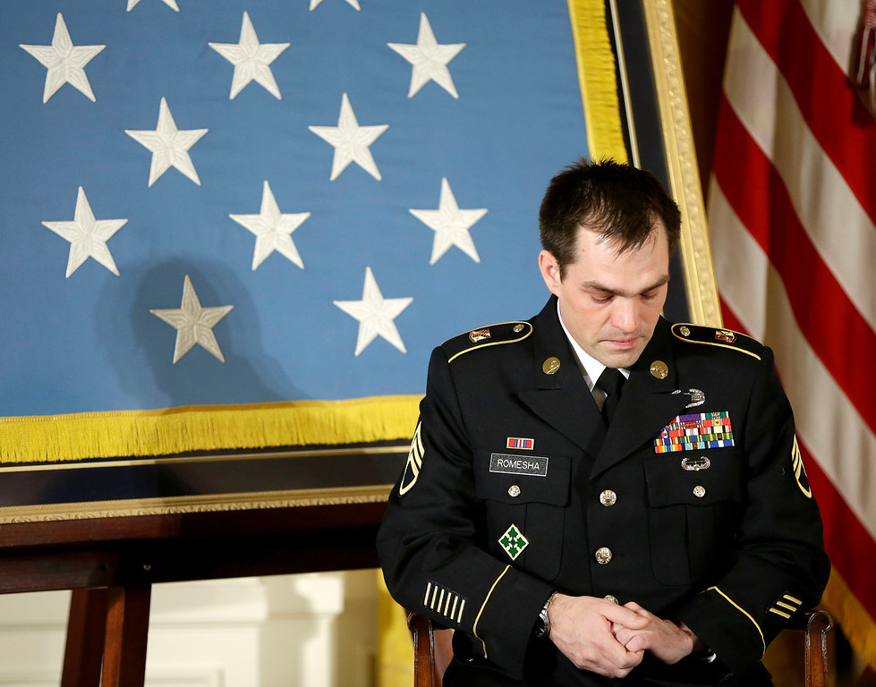 . Medal of Honor recipient, retired Staff Sgt. Clinton Romesha lowers his heads as President Barack Obama speaks about the soldiers lost during an attack on Combat Outpost Keating, Monday, Feb. 11, 2013, during an event in the East Room of the White House in Washington. Romesha\'s leadership during a daylong attack by hundreds of fighters on Combat Outpost Keating in Afghanistan led to award. (AP Photo/Pablo Martinez Monsivais)