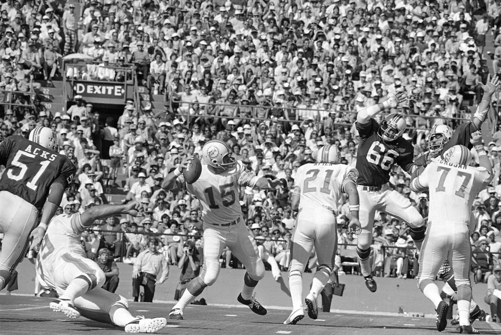 . Miami Dolphins quarterback Earl Morrall gets to hurl another pass in their game against the New England Patriots Sunday afternoon, Nov. 12, 1972 at Miami\'s Orange Bowl. Up in the air to block is Patriot linebacker Ed Weisacosky (66) and blocking for Morrall is Jim Kiick (21). The Dolphins, pro football\'s only undefeated team, enjoyed a 31-0 halftime lead. (AP Photo)