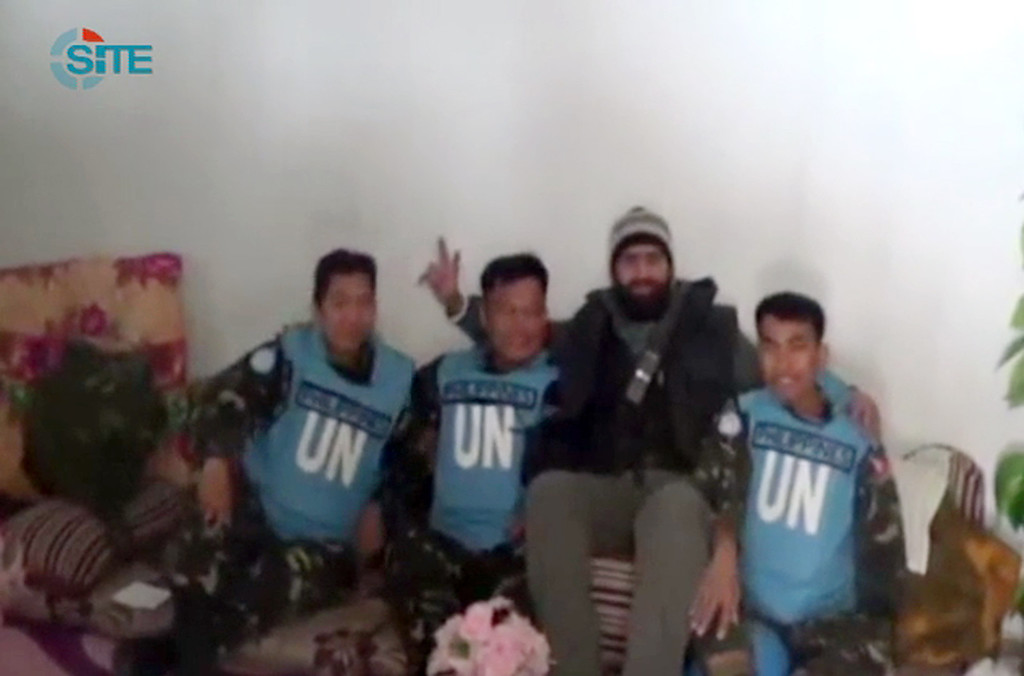 ". This image was taken from video released by the SITE Intelligence Group on March 8, 2013. According to a SITE statement release with the video, ""the al-Yarmouk Martyrs Battalion released a short clip showing a militant commander posing with three Filipino members of the United Nations Disengagement Observer Force (UNDOF) unit that was captured near al-Jamla village in the Golan Heights. The 12-second clip was posted on YouTube on March 8, 2013, and shows a commander in the Free Syrian Army\'s Battalion of the Martyr Ra\'id al-Masri sitting between the captives. In addition, the al-Yarmouk Martyrs Battalion posted an update on its Facebook page about the UNDOF members, informing that it told al-Jazeera it will hand the men over to the Red Cross after Syrian regime forces stop bombing the area of Wadi al-Yarmouk.\"" AFP PHOTO / SITE Intelligence Group"