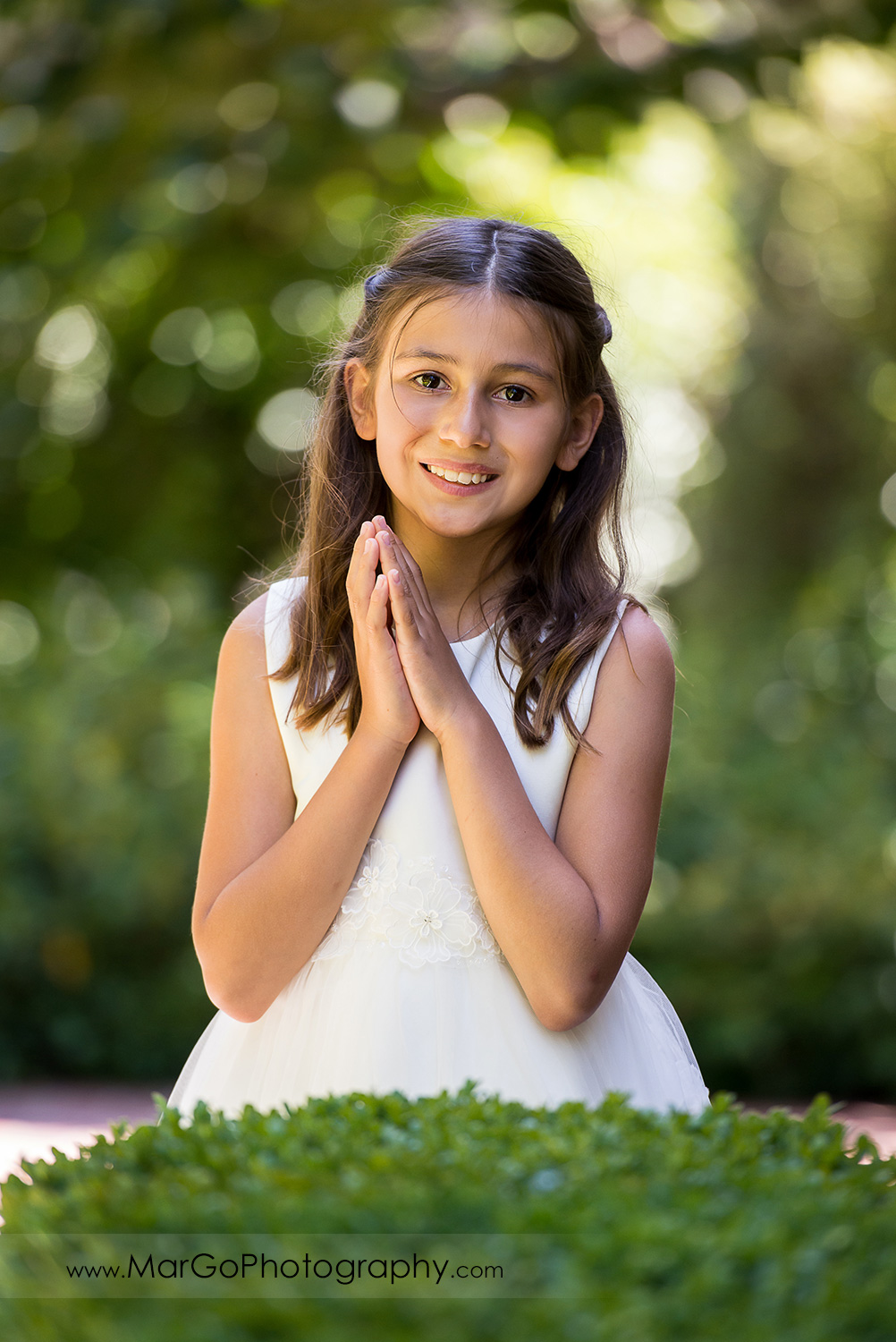 portrait of first communion girl in white dress with folded hands at green background at Cafe Wisteria in Menlo Park