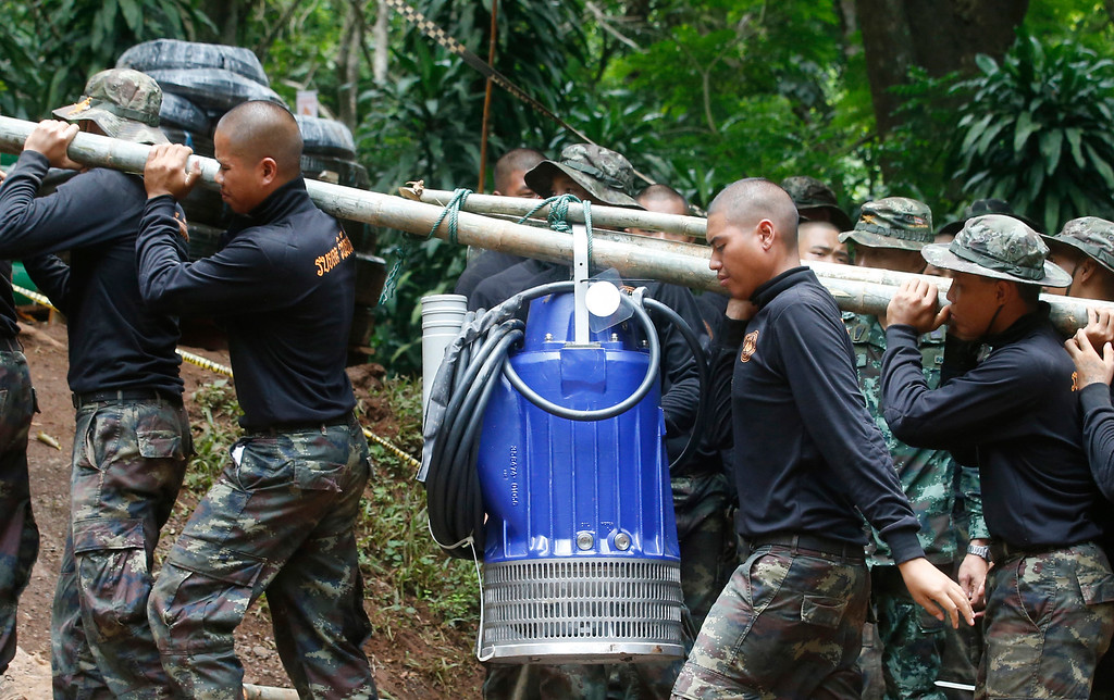 . Soldiers carry a pump to help drain the rising flood water in a cave where 12 boys and their soccer coach have been trapped since June 23, in Mae Sai, Chiang Rai province, in northern Thailand Friday, July 6, 2018. Thai authorities are racing to pump out water from the flooded cave before more rains are forecast to hit the northern region. (AP Photo/Sakchai Lalit)
