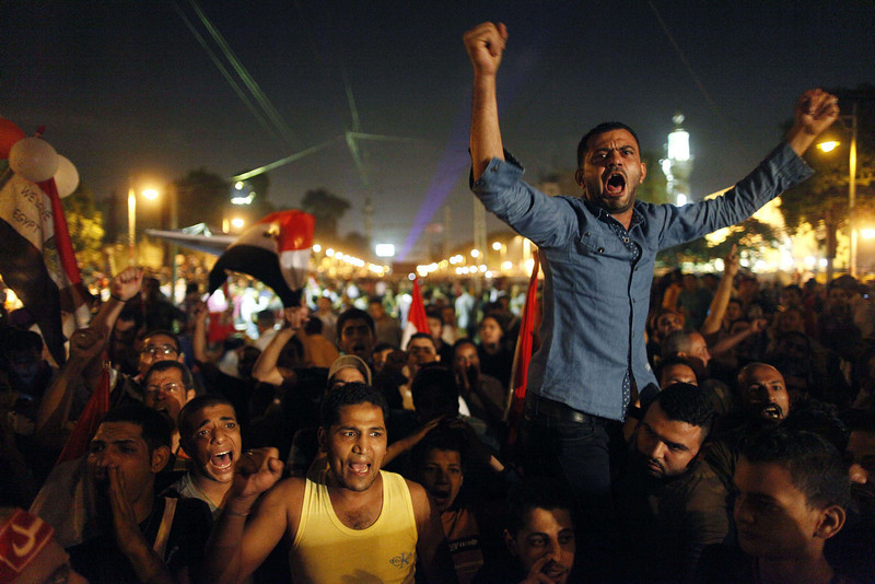 . Egyptian protesters calling for the ouster of President Mohamed Morsi react as they watch his speech on a screen in a street leading to presidential palace early in Cairo on July 3, 2013. Morsi told Egyptians that he had been freely elected little more than a year ago and that he intended to continue to carry out his duties despite mass protests demanding his resignation.  MAHMUD KHALED/AFP/Getty Images