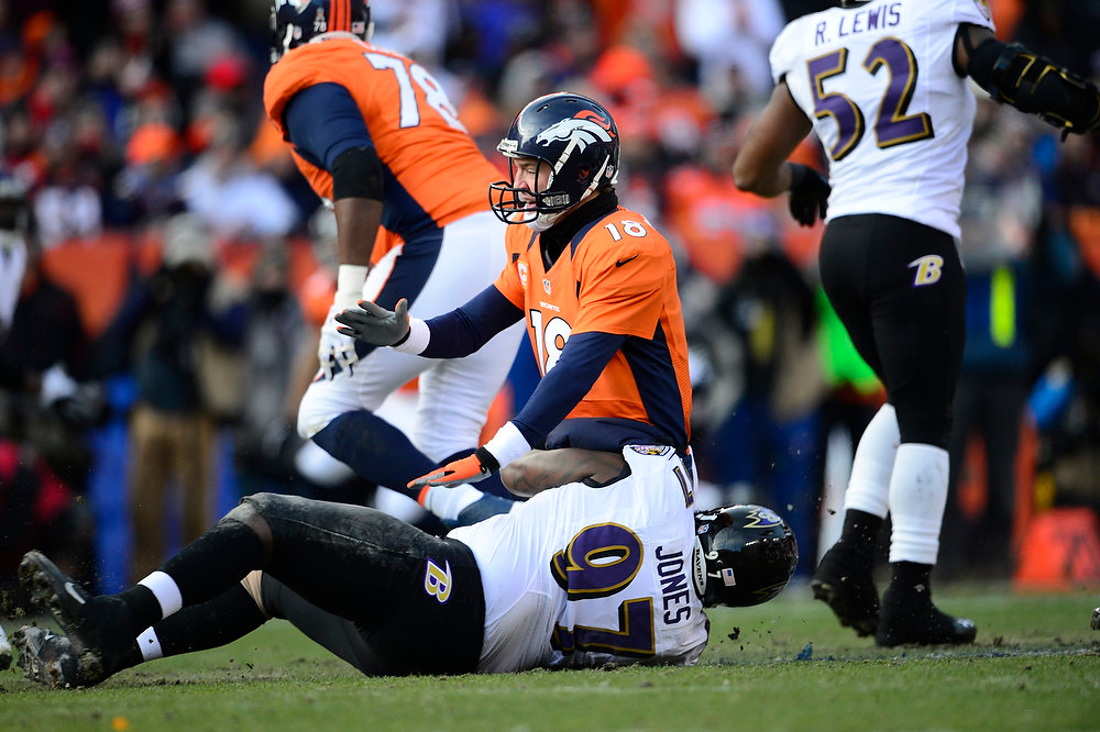Description of . Denver Broncos quarterback Peyton Manning (18) is taken down by Baltimore Ravens defensive end Arthur Jones (97) after releasing the ball in the first quarter. The Denver Broncos vs Baltimore Ravens AFC Divisional playoff game at Sports Authority Field Saturday January 12, 2013. (Photo by AAron  Ontiveroz,/The Denver Post)
