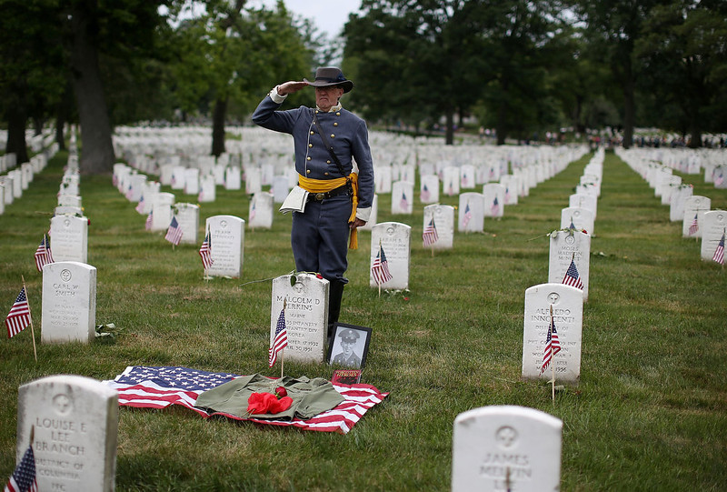 . Civil War reenactor David Hillier salutes while dressed as Col. John S. Mosby while visiting the gravesite of soldier killed during the Korean War, at Arlington Cemetery, May 27, 2013 in Arlington, Virginia. For Memorial Day President Obama layed a wreath at the Tomb of the Unknowns, paying tribute to military veterans past and present who have served and sacrificed their lives for their country.  (Photo by Mark Wilson/Getty Images)