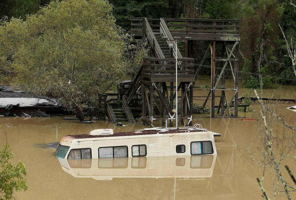 . An RV sits underwater from the flooded  Russian River Friday, Dec. 12, 2014, in Guerneville, Calif.   While the sun rose Friday in a dry San Francisco sky, the storm\'s affects lingered in Northern California. In Sonoma County, the Russian River was approaching flood stage and was expected to crest several feet above it by early afternoon. Officials advised residents of about 300 homes to evacuate low-lying areas. (AP Photo/Eric Risberg)