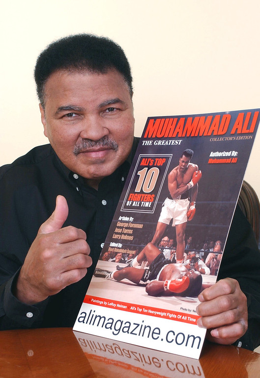 . Boxing legend Muhammad Ali poses with a copy of a new magazine that chronicles his life and career in the ring Monday, March 11, 2002, in Beverly Hills, Calif. The collectible magazine features articles written by former boxing champs and includes paintings, sketches, cartoons and photographs of Ali throughout his career. (AP Photo/Silver Star Media Group, Inc., Rene Macura)