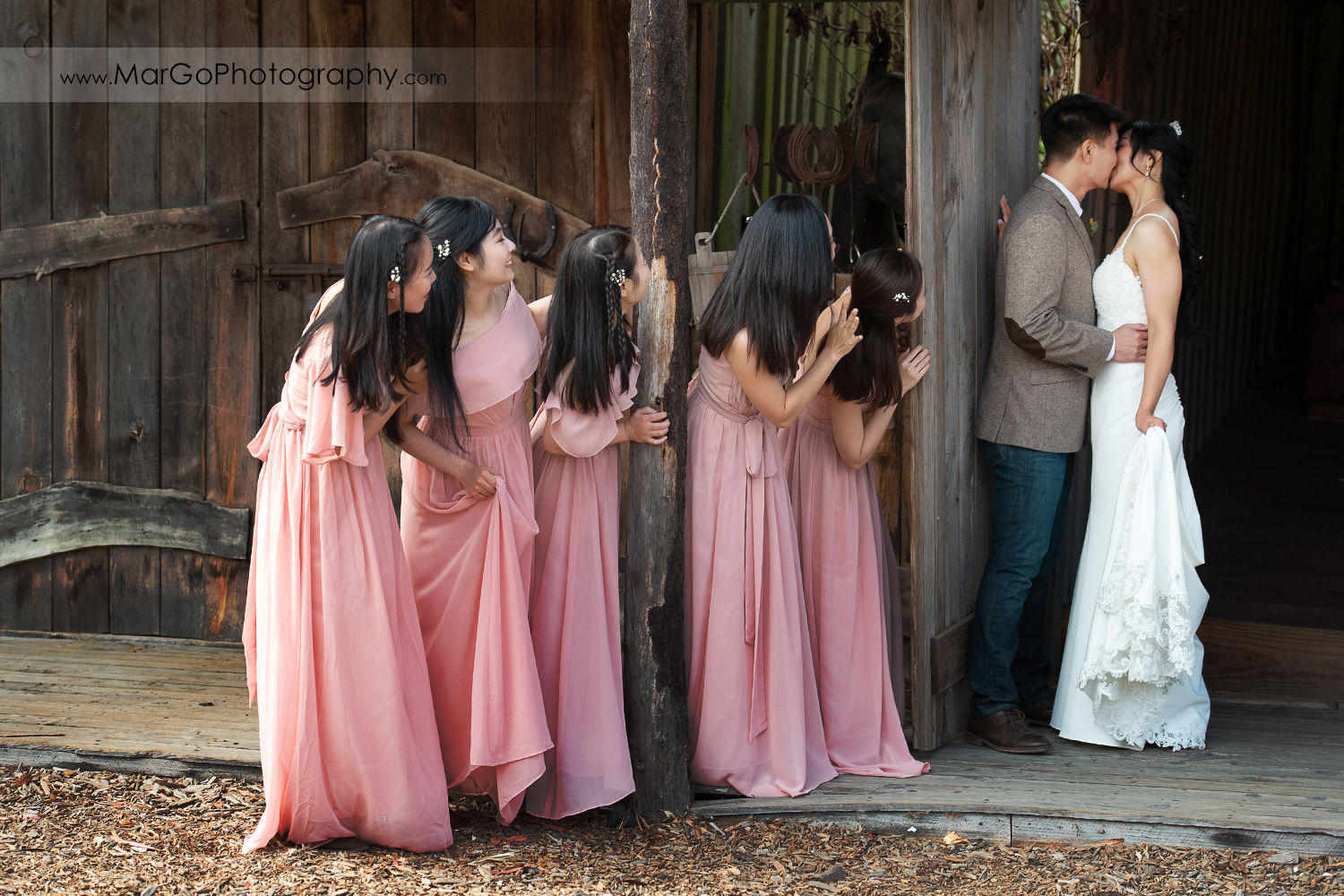 bride and groom kissing with peeping bridesmaids in pink dresses at Long Branch Saloon & Farms in Half Moon Bay