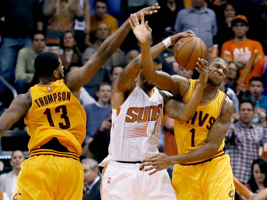 . Cleveland Cavaliers\' James Jones (1) and Tristan Thompson (13) battle Phoenix Suns\' Markieff Morris for a rebound during the second half of an NBA basketball game, Tuesday, Jan. 13, 2015, in Phoenix. The Suns won 107-100. (AP Photo/Matt York)