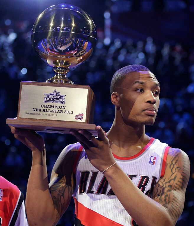 . Damian Lillard of the Portland Trail Blazers raises the trophy after winning the skills challenge during NBA basketball All-Star Saturday Night, Feb. 16, 2013, in Houston. (AP Photo/Eric Gay)