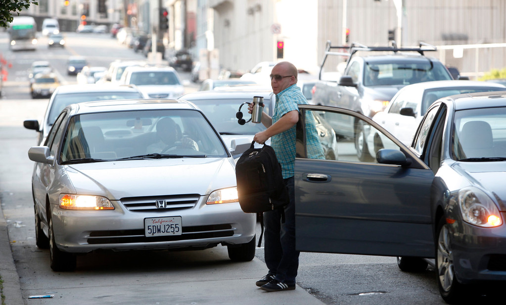 . Clutching his earphones and coffee cup, a casual carpooler exits his transportation after arriving in downtown San Francisco, Calif., on Monday morning July 1, 2013, the first day of the BART strike.  (Karl Mondon/Bay Area News Group)
