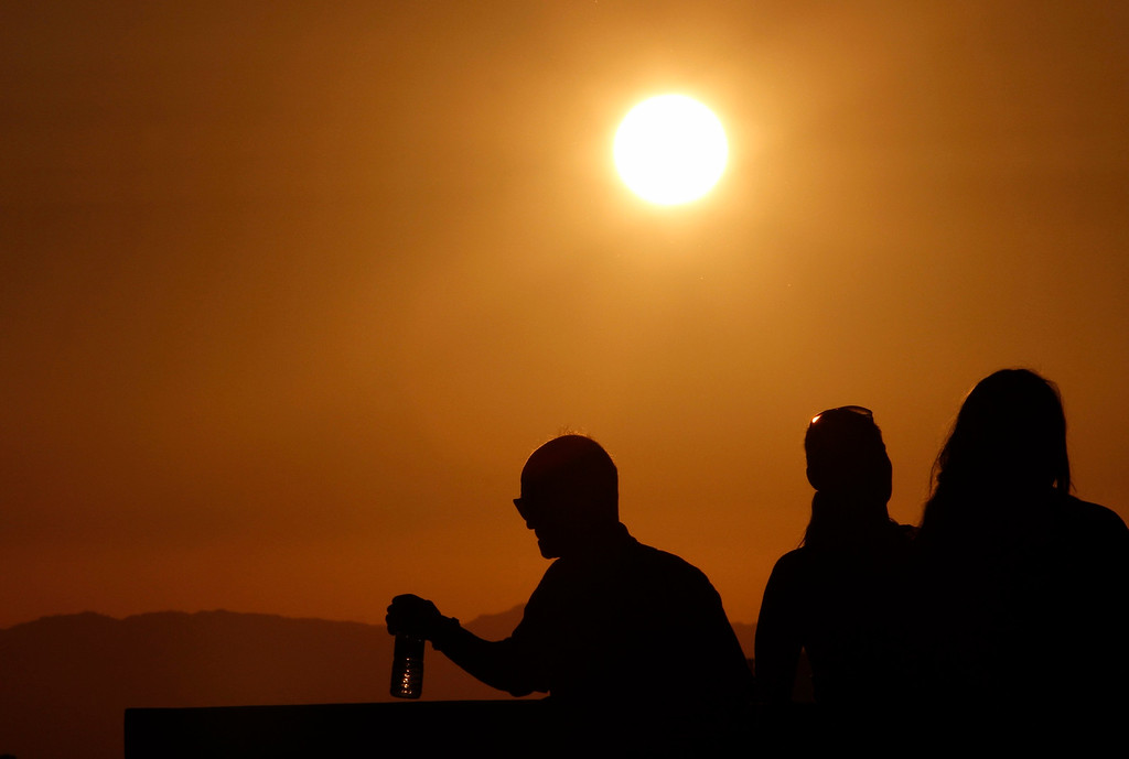 . The sun shines on people standing on the roof observation deck of the Griffith Observatory, as a potentially dangerous heat wave grips the western U.S., in Los Angeles, California, June 29, 2013. Dozens of people were treated for heat-related ailments, and cities and towns across the western United States took emergency measures to help residents cool off, as the region sweltered on Saturday in dangerous triple-digit temperatures. REUTERS/Jonathan Alcorn