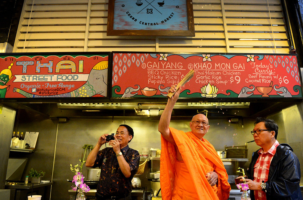 ". Wat Thai Temple\'s head monk Phra Rajthamvites blesses Pasadena resident David Tewasart\'s new business Sticky Rice at Grand Central Market in downtown Los Angeles Monday, April 30, 2013 as he is flanked by Chawapot ""Charlie\"" Thoongsuwan and Surapong \""Mar\"" Chinotaixul. Sticky Rice is kicking off the openings of new restaurants at the market. (SGVN/Staff Photo by Sarah Reingewirtz)"