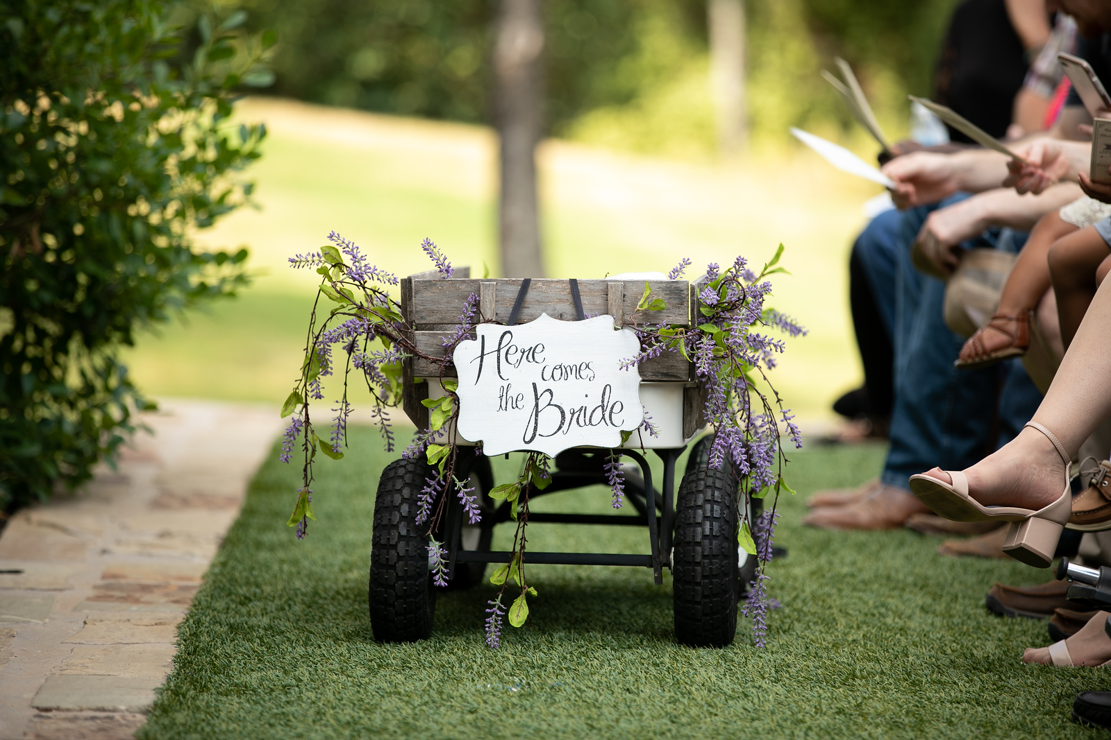 a flower girl rustic wagon decorated with lavender flowers and a sign that says here comes the bride