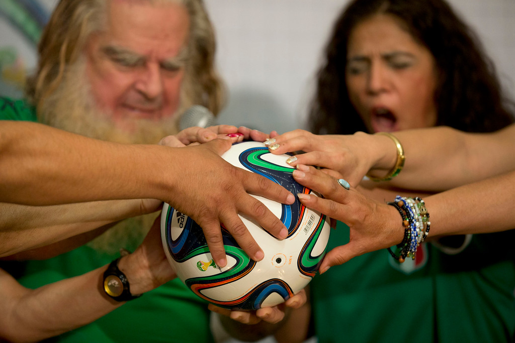 ". Mexico City\'s ""Great Warlock\"" Antonio Vazquez, left, and assistants perform a magic ritual using a soccer ball to help Mexico\'s national soccer team reach the quarter-finals in the World Cup, in Mexico City, Wednesday, June 11, 2014. The ceremony was intended to \""clean\"" the Mexican team of bad vibes and to \""neutralize\"" mystical rituals performed on behalf of the Cameroonian team. (AP Photo/Rebecca Blackwell)"
