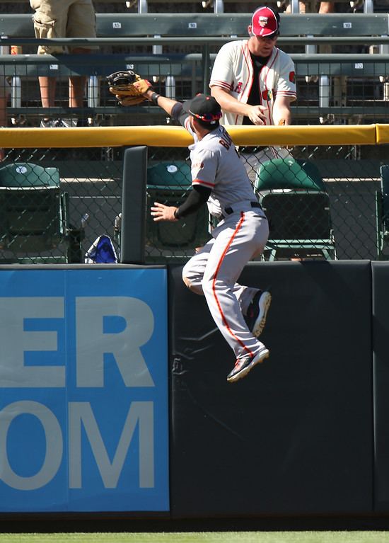 . San Francisco Giants left fielder Gregor Blanco climbs the fence in a failed attempt to catch a three-run home run by Colorado Rockies\' Nolan Arenado in the fifth inning of the Rockies\' 9-2 victory in a baseball game in Denver on Wednesday, Sept. 3, 2014. (AP Photo/David Zalubowski)