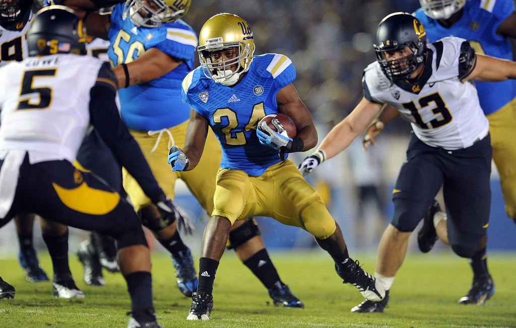 . UCLA running back Paul Perkins (24) runs through the California defense for a first down during the first half of their college football game in the Rose Bowl in Pasadena, Calif., on Saturday, Oct. 12, 2013.   (Keith Birmingham Pasadena Star-News)