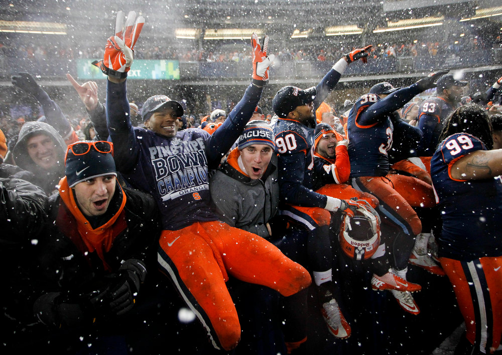 Description of . Members of the Syracuse Orange celebrate with fans after their win over the West Virginia Mountaineers in the New Era Pinstripe Bowl at Yankee Stadium on December 29, 2012 in the Bronx borough of New York City.  (Photo by Jeff Zelevansky/Getty Images)