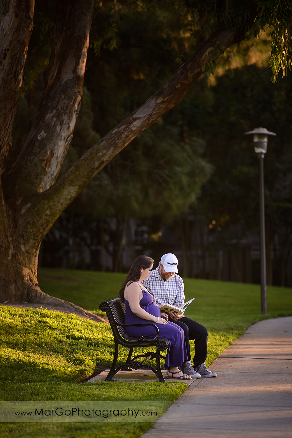 man in checkered shirt and pregnant woman in long violet dress sitting on the bench and reading children book at Lick Mill Park in Santa Clara
