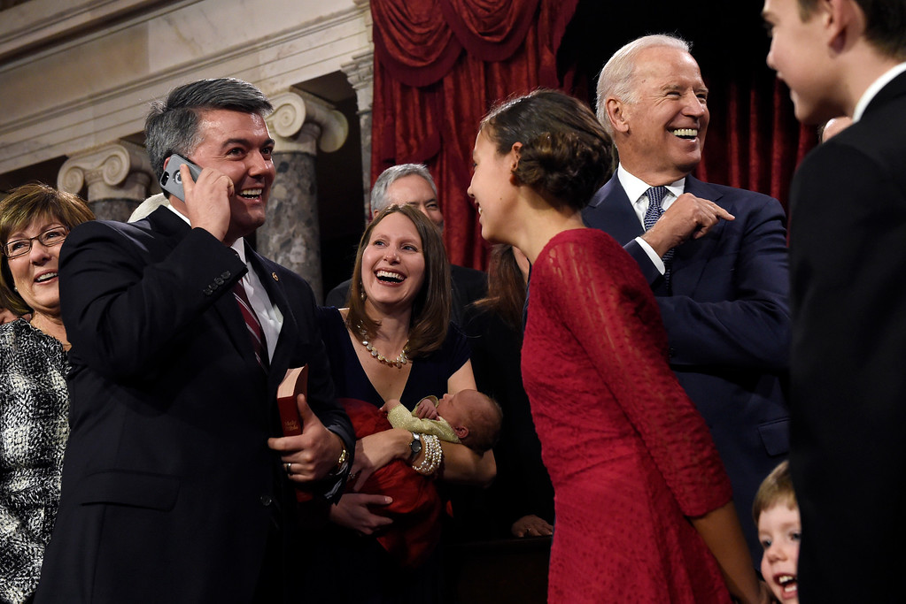 . Sen. Cory Gardner R-Colo. talks on the phone with his 91-year-old grandmother Betty Pagel of Yuma, Colo., after he was administered the Senate oath by Vice President Joe Biden, second from right, following a ceremonial re-enactment swearing-in ceremony, Tuesday, Jan. 6, 2015, in the Old Senate Chamber on Capitol Hill in Washington. (AP Photo/Susan Walsh)
