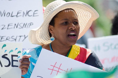 KITCHENER, Ont. (23/07/2016) - Monica Kandjoje leads sing Zimbabwean songs.  Members of the Zimbabwe Canada Association of Waterloo, gather together at Victoria Park for a peaceful march to draw attention to government and human rights violations in Zimbabwe. There has been a civic unrest across the country without response from the government. #thisflag is the hash tag created by Pastor Evan Mawarire to begin a boycott earlier this month to bring awareness to what in happening in Zimbabwe.  Rev. James Kandoje, President of the association led the march from Victoria Park to Kitchener City Hall via Jacob, Queen, and King St.  Photos by Alicia Wynter/The Record