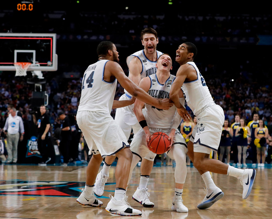 . Villanova guard Donte DiVincenzo, center, celebrates with teammates at the end of the championship game against Michigan in the Final Four NCAA college basketball tournament, Monday, April 2, 2018, in San Antonio. Villanova won 79-62. (AP Photo/David J. Phillip)