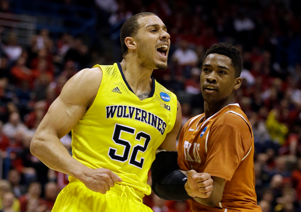 Description of . Michigan forward Jordan Morgan (52) reacts to a foul call as Texas guard Isaiah Taylor watches him during the second half of a third-round game of the NCAA college basketball tournament Saturday, March 22, 2014, in Milwaukee. (AP Photo/Jeffrey Phelps)