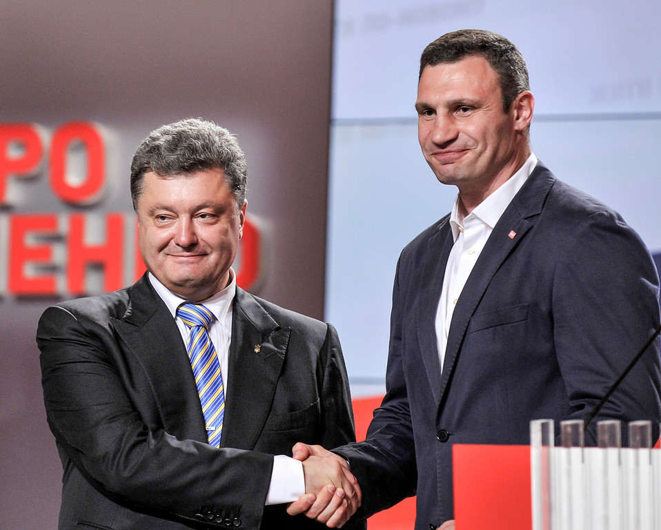 . Ukrainian presidential candidate Petro Poroshenko, left, shake hands with Vitali Klitschko during their press conference in Kiev, Ukraine, Sunday, May 25, 2014. An exit poll showed that billionaire candy-maker Petro Poroshenko won Ukraine\'s presidential election and Vitali Klitschko won Kiev\'s mayoral  outright Sunday in the first round ó a vote that authorities hoped would unify the fractaured nation. (AP Photo/Mykola Lazarenko, Pool)