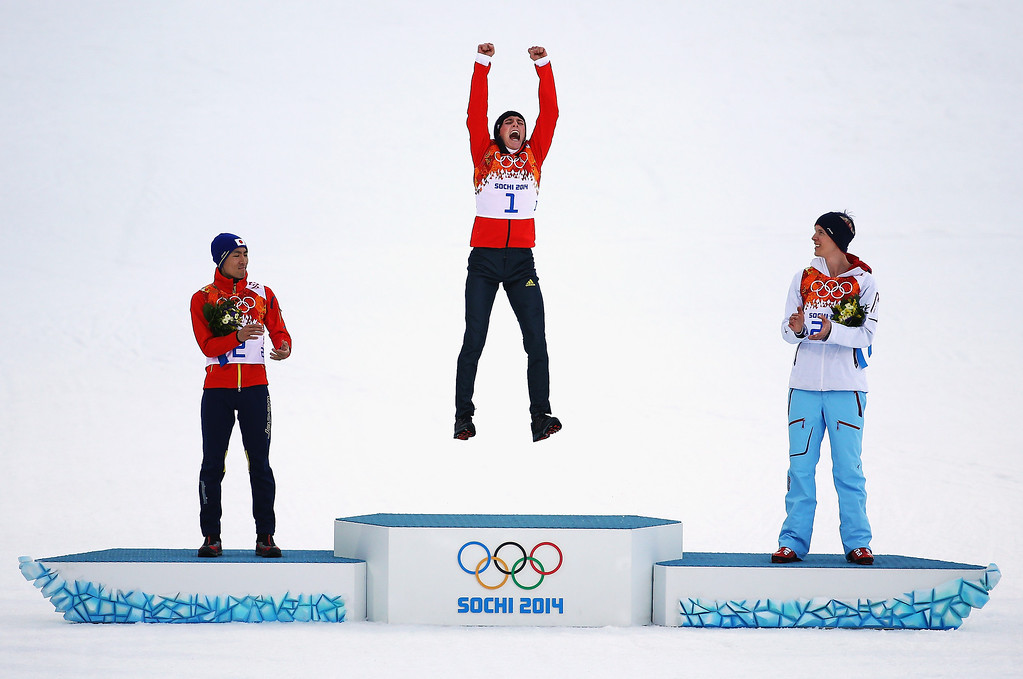 . Gold medalist Eric Frenzel of Germany jumps in celebration alongside silver medalist Akito Watabe of Japan (L) and bronze medalist Magnus Krog of Norway (R) during the flower ceremony for the Men?s Nordic Combined Individual Gundersen Normal Hill and 10km Cross Country on day 5 of the Sochi 2014 Winter Olympics at the RusSki Gorki Nordic Combined Skiing Stadium on February 12, 2014 in Sochi, Russia.