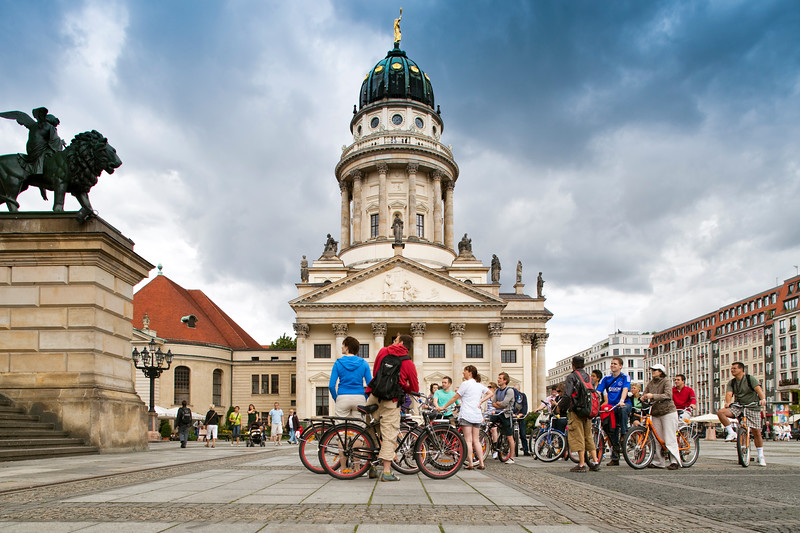 Cyclists on Gendarmenmarkt square, with the French Cathedral (Französische Dom) on the background, Berlin, Germany