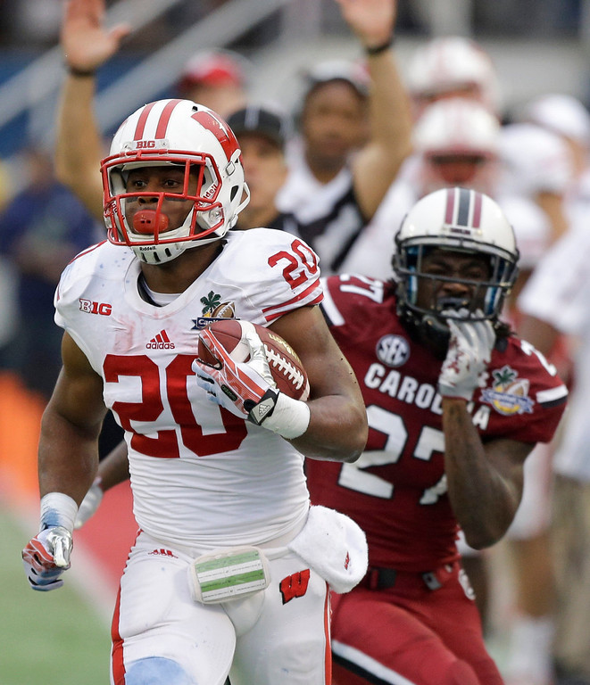 . Wisconsin running back James White (20) gets past South Carolina cornerback Victor Hampton (27) for a short gain during the first half of the Capital One Bowl NCAA college football game in Orlando, Fla., Wednesday, Jan. 1, 2014.(AP Photo/John Raoux)