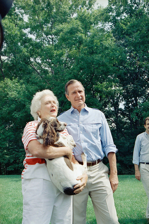. Vice President George H.W. Bush, right, and his Barbara Bush, holding the family dog, talk to reporters after a press conference outside their home, Sept. 3, 1988, Washington, D.C. Bush said he was standing firm on his proposal for just two presidential debates even though Democratic rival Michael Dukakis, who he called a better debater, wants three, Bush commenting about his debating skills, added tongue-in-cheek: I\'m lowering expectations. My wife Barbara, when I practice debating, she falls asleep. Mrs. Bush, told reporters later Bush\'s comments were not true. (AP Photo/J. Scott Applewhite)