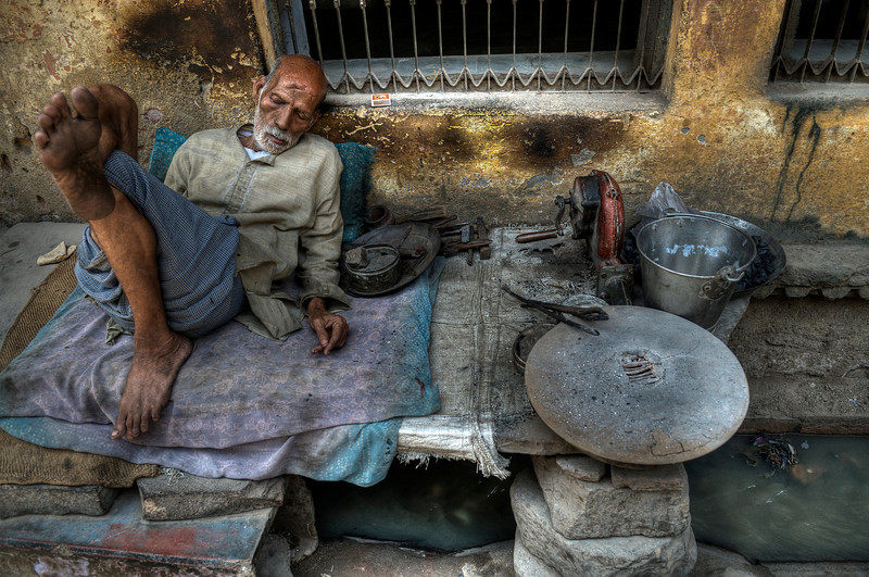 Most Indian towns still have open sewage systems. This metal worker takes a nap by his road side workshop.  Raw sewage flows beneath him.  Bundi, Rajasthan, 2011.