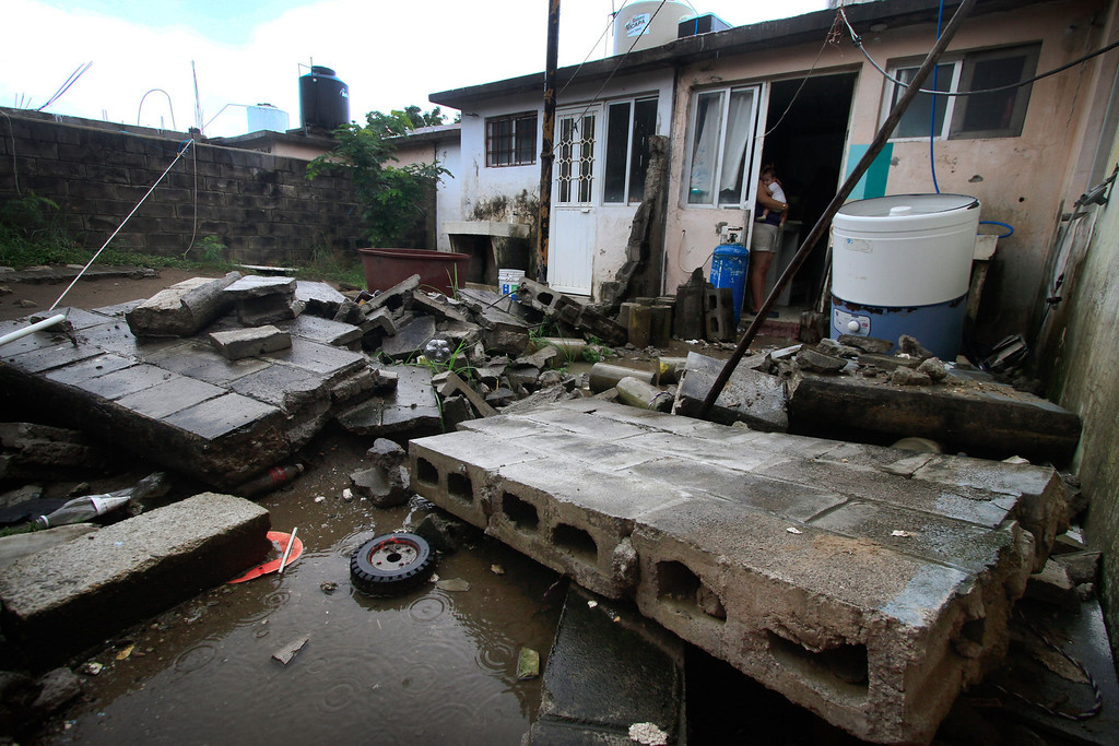 . A woman holds her baby while standing at the door of her damaged house in Veracruz, Mexico, on September 17, 2013 following heavy rains in the country. Mexican authorities scrambled Tuesday to launch an air lift to evacuate tens of thousands of tourists stranded amid floods in the resort of Acapulco following a pair of deadly storms. At least 48 people were killed and thousands evacuated from towns on the Pacific and Gulf of Mexico coasts over the weekend as Tropical Storm Manuel and downgraded Hurricane Ingrid set off landslides and floods that damaged bridges, roads and homes.  KORAL CARBALLO/AFP/Getty Images