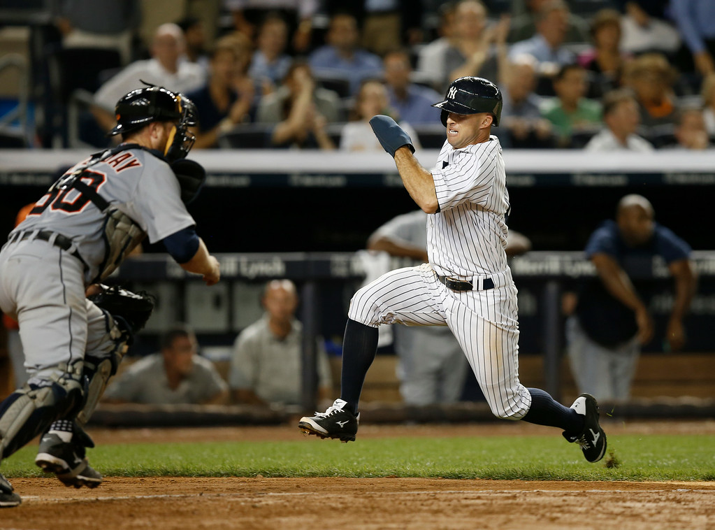 . New York Yankees Brett Gardner heads home to score in front of Detroit Tigers catcher Bryan Holaday (50) in a baseball game at Yankee Stadium in New York, Wednesday, Aug. 6, 2014.  (AP Photo/Kathy Willens)