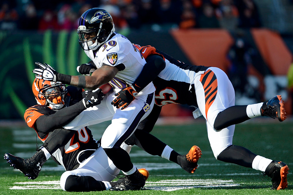 Description of . Cincinnati Bengals outside linebacker Vontaze Burfict (55) and strong safety Taylor Mays tackle Baltimore Ravens running back Bernard Pierce (30) in the first half of an NFL football game, Sunday, Dec. 30, 2012, in Cincinnati. (AP Photo/Michael Keating)