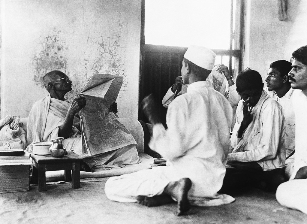 . Mahatma Gandhi reading The Times newspaper with staff around April 23, 1930. (AP Photo)