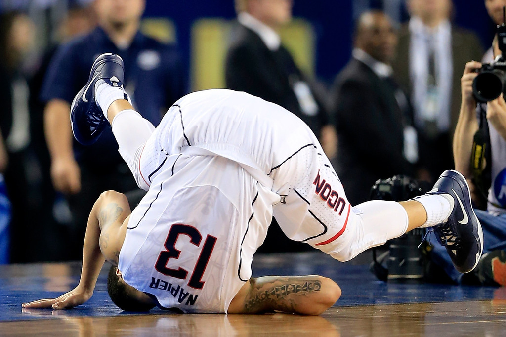 . ARLINGTON, TX - APRIL 07: Shabazz Napier #13 of the Connecticut Huskies falls to the ground during the NCAA Men\'s Final Four Championship against the Kentucky Wildcats at AT&T Stadium on April 7, 2014 in Arlington, Texas.  (Photo by Jamie Squire/Getty Images)