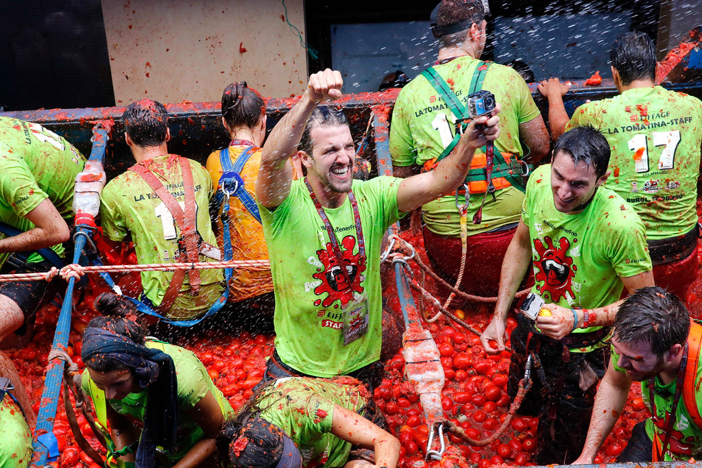 ". People react as they throw tomatoes at each other, during the annual ""tomatina\"" tomato fight fiesta in the village of Bunol, 50 kilometers outside Valencia, Spain, Wednesday, Aug. 30, 2017. (AP Photo/Alberto Saiz)"