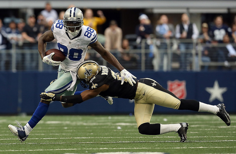 . Wide receiver Dez Bryant #88 of the Dallas Cowboys carries the ball against cornerback Patrick Robinson #21 of the New Orleans Saints at Cowboys Stadium on December 23, 2012 in Arlington, Texas. The New Orleans Saints beat the Dallas Cowboys 34-31 in overtime.  (Photo by Tom Pennington/Getty Images)