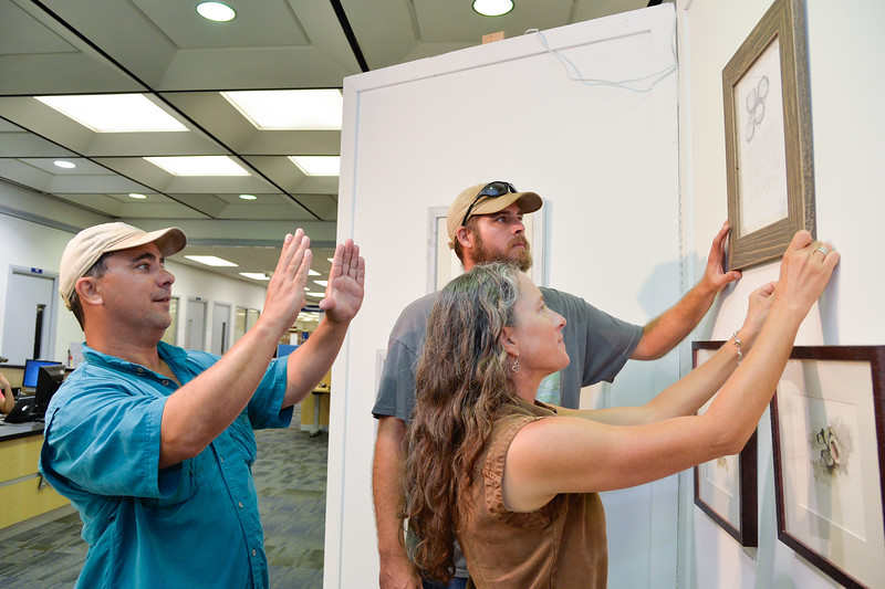 """Mr. Robert Duke(left), Aaron Baxter and Ms. Beth Almaraz prepare for Dr. David Tripp exhibition """"Artist in Residence Program"""" in Mary and Jeff Bell library."""