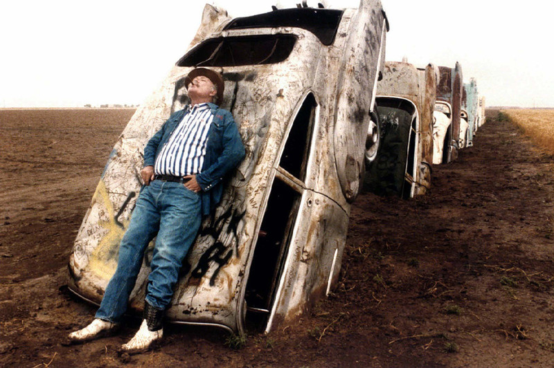 . In this June 1984 file photo, Stanley Marsh 3 leans on one of the 10 Cadillacs buried down on his ranch west of Amarillo, Texas, along old Route 66. Stanley Marsh 3, whose partially buried row of Cadillacs became a road-side tourist attraction in the 1970s, died Tuesday, June 17, 2014. He was 76. (AP Photo/The Dallas Morning News, Evans Caglage, File)