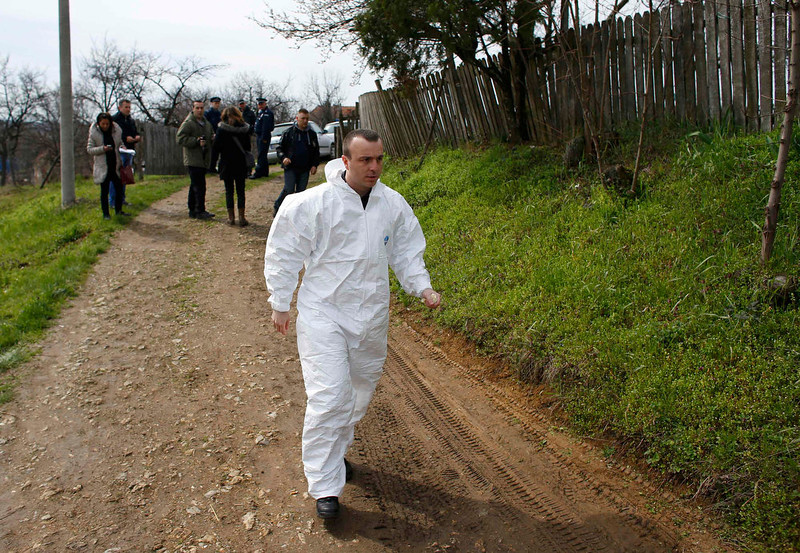 . A forensic expert walks in the village of Velika Ivanca, about 40 km (25 miles) southwest of Belgrade April 9, 2013. A gunman shot dead 13 people, including his mother and son, in an early-morning rampage through a small Serbian village southwest of the capital Belgrade on Tuesday, authorities said. Those killed included a two-year-old child. The gunman, identified by police as Ljubisa Bogdanovic - a war veteran born in 1953 - also shot his wife before turning the gun on himself. Both were in critical condition in hospital, police said.     REUTERS/Marko Djurica