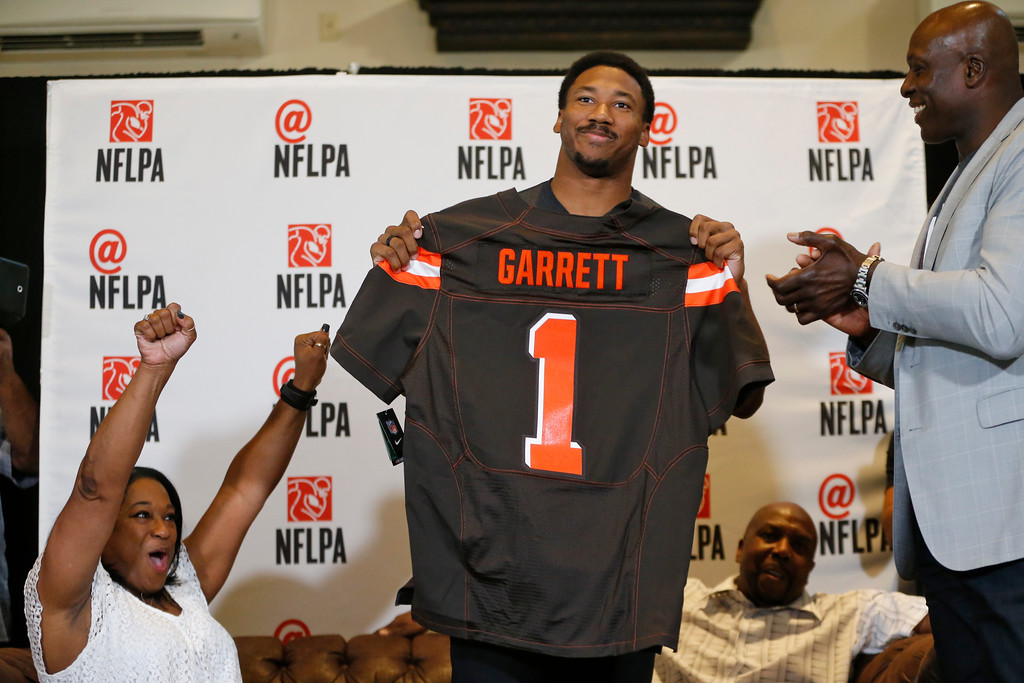 . Texas A&M\'s Myles Garrett holds up a Cleveland Browns jersey as his mother, Audrey Garrett, left, cheers with Bruce Smith, right, after Garrett was taken as the No. 1 pick in the NFL football draft, at Terre Verde Golf Course in Arlington, Texas, Thursday, April 27, 2017. (Nathan Hunsinger/The Dallas Morning News via AP)