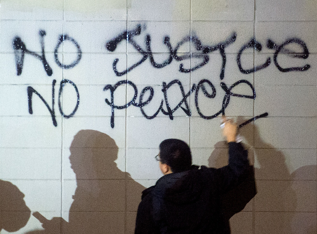 . A demonstrator paints protest graffiti in Oakland, Calif., on Monday, Nov. 24, 2014,  after the announcement of the grand jury decision not to indict Ferguson police officer Darren Wilson in the fatal shooting of Michael Brown, an unarmed 18-year-old. (AP Photo/Noah Berger)